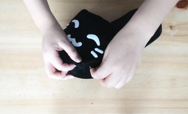 unión y costura de partes para pantuflas de tela en forma de gatito