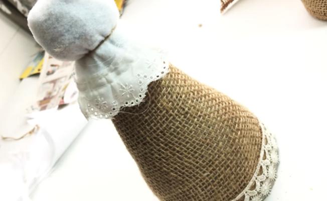colocación de cinta decorativa debajo de cabeza de angelito de tela