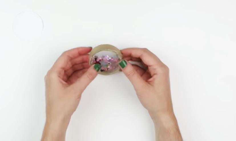 pegado de plástico restante a circulo de cartón para caleidoscopio decorado en tela
