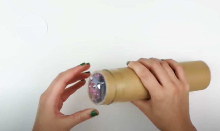 pegado cartón con plásticos a tubo para caleidoscopio decorado en tela